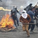 Anti-government demonstrators run from from police during clashes in Quito, Ecuador, Friday, Oct. 11, 2019. Protests, which began when President Lenin Moreno's decision to cut subsidies led to a sharp increase in fuel prices, have persisted for days. (AP Photo/Dolores Ochoa)