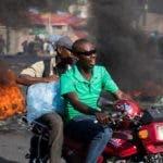HAI01. PUERTO PRÍNCIPE (HAITÍ), 15/10/2019.- Personas esquivan una barricada este martes durante una protesta contra el Gobierno, en Puerto Príncipe (Haití). Naciones Unidas cerró este martes oficialmente su misión de paz en Haití y lo hizo preocupada por la grave crisis que atraviesa el país, con protestas violentas para exigir la salida del presidente, Jovenel Moise. EFE/Orlando Barría
