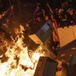 Protesters throw cartons to a burning barricade during clashes with police in Barcelona, Spain, Tuesday, Oct. 15, 2019. Spain's Supreme Court on Monday convicted 12 former Catalan politicians and activists for their roles in a secession bid in 2017, a ruling that immediately inflamed independence supporters in the wealthy northeastern region. (AP Photo/Bernat Armangue)