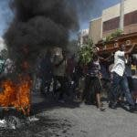 Mourners walk past burning tires as they carry the coffin of one of the people killed during a month of demonstrations aimed at ousting President Jovenel Moïse, as they make their way to a cemetery in central Port-au-Prince, Haiti, Wednesday, Oct. 16, 2019. Funerals for 11 of at least 20 people killed were held in six cities, including the capital of Port-au-Prince, where at least two people were injured in a protest that broke out when presidential guards tried to block a road near where hundreds had gathered around the coffins of two victims. (AP Photo/Rebecca Blackwell)