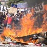 AME3572. SANTIAGO (CHILE), 22/10/2019.- Manifestantes gritan arengas tras una barricada en llamas durante una nueva jornada de protestas este martes, en Santiago (Chile). Un nuevo toque de queda se decretó para la noche de este martes en diferentes ciudades de Chile y es el cuarto consecutivo en Santiago, Valparaíso y Concepción (sur) desde que se registran las protestas que ya dejan unos 15 muertos, informaron hoy las autoridades de los diferentes cuerpos de las fuerzas Armadas. Este martes se volvieron a reproducir manifestaciones en ciudades de todo el país en la quinta jornada consecutiva de protestas en las que se han registrado incendios y saqueos que dejan hasta el momento 15 fallecidos, entre ellos 4 extranjeros provenientes de Colombia, Perú y Ecuador. EFE/ Alberto Valdes