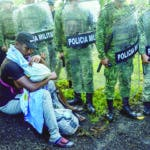 A migrant tends to a child while surrounded by members of the National Guard near Tuzantan, Chiapas state, Mexico, Saturday, Oct. 12, 2019. Hundreds of migrants were arrested by Mexican authorities as they made their way to Mexico City. (AP Photo/Isabel Mateos)