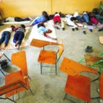 A group of 16 students at Haiti's State University, who didn't want their identities revealed to protect their safety, rest in a classroom on day three of a hunger strike calling for the resignation of President Jovenel Moïse and protesting against insecurity, inflation, corruption, and other societal ills, in Port-au-Prince, Haiti, Tuesday, Oct. 15, 2019. Haiti's embattled president faced a fifth week of protests as road blocks and marches continue across the country, after opposition leaders said they will not back down on their call for Moïse to resign. (AP Photo/Rebecca Blackwell)