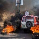 """AME2840. PUERTO PRÍNCIPE (HAITÍ), 10/11/2019.- Una ambulancia pasa en medio de una calle con llantas quemándose parte de una protesta contra el presidente de Haití, Jovenel Moise, este domingo en Puerto Príncipe (Haití). La oposición en Haití realizó nuevas protestas un día después de que se anunciase un acuerdo para una """"transición"""", que se pondría en marcha si el mandatario renunciase. EFE/Jean Marc Havelard."""