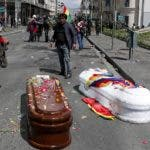 Coffins containing the remains of people killed during clashes between security forces and supporters of former President Evo Morales, lay in the middle of a street after police launched tear gas at a massive funeral procession to disperse anti-government protesters accompanying the coffins into La Paz, Bolivia, Thursday, Nov. 21, 2019. Bolivia has been in a state of turbulence since Morales resigned Nov. 10 after weeks of protests against him over a disputed vote that, according to an international audit, was marred by irregularities. (AP Photo/Juan Karita)