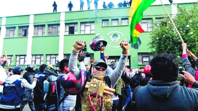 AME1953. COCHABAMBA (BOLIVIA), 08/11/2019.- Policías bolivianos saludan desde el techo de una unidad policial a ciudadanos apostados en las puertas de la misma este viernes 8 de noviembre en Cochabamba (Bolivia). Un grupo de policías se amotinó este viernes en un cuartel de la ciudad boliviana de Cochabamba en protesta contra el Gobierno del presidente de Bolivia, Evo Morales, sin que aún haya un pronunciamiento oficial. EFE/Jorge Abrego