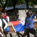 Protesters carry a coffin that contains the remains of a fellow protester, in Port-au-Prince, Haiti, Tuesday, Nov. 19, 2019. Hundreds of people attended the funerals for five people killed during anti-government protests, three of whom were allegedly shot by police while participating in the protests. (AP Photo/Dieu Nalio Chery)