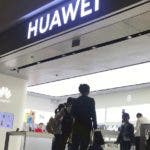 People look at a Huawei store in Shenzhen Bao'an International Airport in Shenzhen in southern China's Guangdong Province, Friday, Nov. 15, 2019. Chinese tech giant Huawei is selling its first folding smartphone without Google apps or U.S.-made processor chips following sanctions imposed by Washington. (AP Photo/Olivia Zhang)