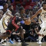 Miami Heat guard Kendrick Nunn, center, drives to the basket as New Orleans Pelicans guard E'Twaun Moore, left, and forward Derrick Favors, right, defend during the first half of an NBA basketball game, Saturday, Nov. 16, 2019, in Miami. (AP Photo/Lynne Sladky)