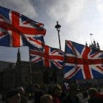 Union flags are waved by pro Brexit supporters outside the Houses of Parliament, in London, Thursday, Oct. 31, 2019. Finally, Britain's political ice floes are moving. After three years of Brexit impasse, an election in six weeks may break the logjam. Or it may just rearrange the ice pack, keeping the U.K. trapped half in and half out of the European Union.(AP Photo/Alberto Pezzali)