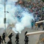 Riot police fire tear gas as supporters of the Movimiento Al Socialismo (MAS) party, of Bolivian President Evo Morales, confront supporters of the Comunidad Ciudadana (CC) opposition party, of former presidential candidate Carlos Mesa, during a strike in Santa Cruz on October 28, 2019. - The platform gathering the regional civic committees (Conade), demanded the annulment of the controversial general elections in Bolivia, won by President Evo Morales in the first round, and called for new elections with a new electoral court. (Photo by DANIEL WALKER / AFP) / The erroneous mention appearing in the metadata of this photos by DANIEL WALKER has been modified in AFP systems in the following manner: [in Santa Cruz] instead of [in La Paz]. Please immediately remove the erroneous mention from all your online services and delete them from your servers. If you have been authorized by AFP to distribute it (them) to third parties, please ensure that the same actions are carried out by them. Failure to promptly comply with these instructions will entail liability on your part for any continued or post notification usage. Therefore we thank you very much for all your attention and prompt action. We are sorry for the inconvenience this notification may cause and remain at your disposal for any further information you may require. (Photo by DANIEL WALKER/AFP via Getty Images)