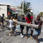 Demonstrators down an electricity pole to block a street as they demand the resignation of President Jovenel Moise, in Port-au-Prince, Haiti, Friday, Nov. 1, 2019. Anger over corruption, inflation and scarcity of basic goods, including fuel, has led to more than a month of demonstrations that have paralyzed the country as protesters demand the resignation of President Jovenel Moise. (AP Photo/Dieu Nalio Chery)