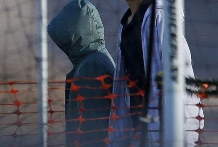 File-In this Dec. 13, 2018, file photo, teen migrants walk in line inside the Tornillo detention camp in Tornillo, Texas. Government investigators say many more migrant children may have been separated from their parents than the Trump administration has acknowledged.  (AP Photo/Andres Leighton, File)