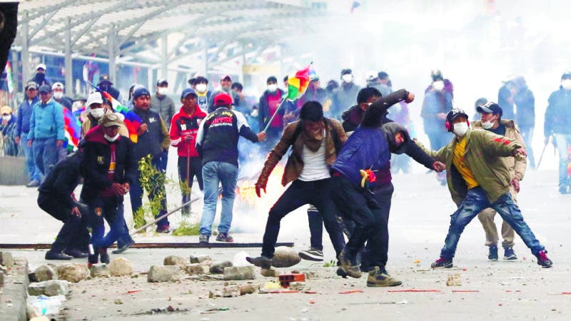 Backers of former President Evo Morales clash with police in La Paz, Bolivia, Wednesday, Nov. 13, 2019. Bolivia's new interim president Jeanine Anez faces the challenge of stabilizing the nation and organizing national elections within three months at a time of political disputes that pushed Morales to fly off to self-exile in Mexico after 14 years in power. (AP Photo/Natacha Pisarenko)
