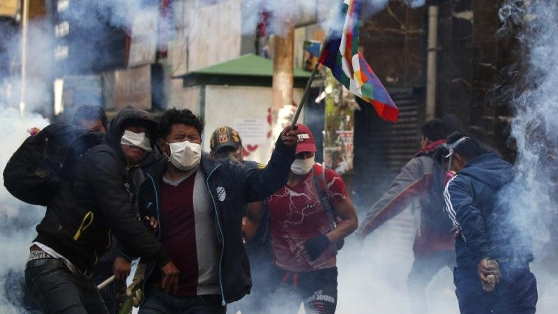 Police launch tear gas to disperse the supporters of former President Evo Morales in La Paz, Bolivia, Friday, Nov. 15, 2919. Bolivia's new interim president Jeanine Anez faces the challenge of stabilizing the nation and organizing national elections within three months at a time of political disputes that pushed Morales to fly off to self-exile in Mexico after 14 years in power. (AP Photo/Natacha Pisarenko)