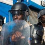 """AME2852. PUERTO PRÍNCIPE (HAITÍ), 10/11/2019.- Integrantes de la Policía de Haití vigilan durante una protesta contra el presidente de Haití, Jovenel Moise, este domingo en Puerto Príncipe (Haití). La oposición en Haití realizó nuevas protestas un día después de que se anunciase un acuerdo para una """"transición"""", que se pondría en marcha si el mandatario renunciase. EFE/Jean Marc Havelard."""