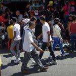 AME4415. CARACAS (VENEZUELA), 09/12/2019.- Un grupo de personas caminan en un mercado popular este lunes, en Caracas (Venezuela). La inflación venezolana subió el pasado noviembre hasta el 35,8 %, casi el doble del marcador de octubre, cuando se registró un 20,7 %, lo que recuerda a los venezolanos que el país caribeño está, según indicó este lunes el Parlamento -de mayoría opositora-, lejos de superar la crisis económica. EFE/ Rayner Peña