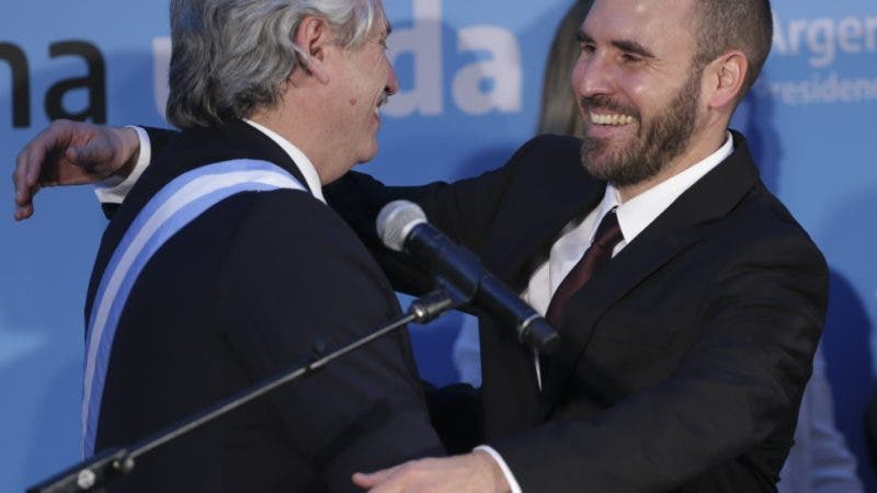 Argentina's President Alberto, left, embraces Martin Guzman after appointing him finance minister at the presidential palace in Buenos Aires, Argentina, Tuesday, Dec. 10, 2019. Fernandez became president of Argentina on Tuesday, returning the country's Peronist political movement to power amid an economic crisis and rising poverty. (AP Photo/Daniel Jayo)