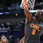 Orlando Magic guard Terrence Ross (8) dunks over New Orleans Pelicans forward Derrick Favors, left, and guard Frank Jackson in the first half of an NBA basketball game in New Orleans, Sunday, Dec. 15, 2019. (AP Photo/Gerald Herbert)