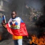 A demonstrator draped in the Haitian flag, holds up a copy of the Haitian constitution, during a protest to demand the resignation of President Jovenel Moise and demanding to know how Petro Caribe funds have been used by the current and past administrations, in Port-au-Prince, Haiti, Thursday, Feb. 7, 2019. Much of the financial support to help Haiti rebuild after the 2010 earthquake comes from Venezuela's Petro Caribe fund, a 2005 pact that gives suppliers below-market financing for oil and is under the control of the central government. (AP Photo/Dieu Nalio Chery)