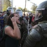 A demonstrator argues with an anti riot police officer during a protest in Santiago, Chile, Monday, Dec. 9, 2019. Student protests have become a nationwide call for socio-economic equality and better social services, so far forcing Chilean President Sebastian Pinera to increase benefits for the poor and disadvantaged and start a process of constitutional reform. (AP Photo/Fernando Llano)