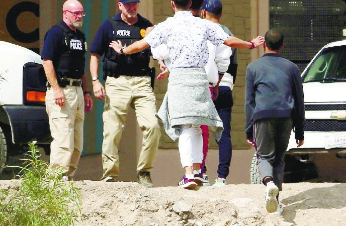 FILE - In this July 4, 2019 file photo, a group of asylum seekers cross the border between El Paso, Texas, and Juarez, Chihuahua, Mexico, Thursday, July 4, 2019. A lawsuit claims a new effort to speed up initial reviews of asylum claims to within three days denies asylum-seekers rights to consult attorneys. It is the latest challenge to the Trump administration's efforts to change asylum policies and practices since the U.S. became the world's top destination for asylum-seekers in 2017. (Mark Lambie/The El Paso Times via AP, File)