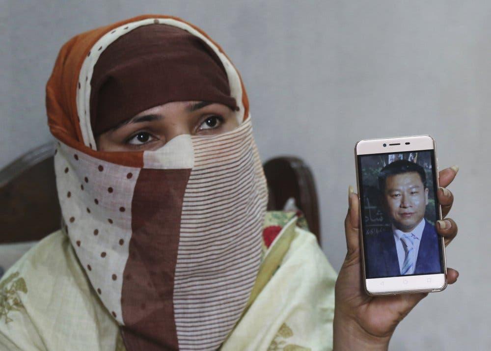 Sumaira muestra una foto del chino con que se casó. La mujer, quien no quiso dar su apellido, dice que fue violada reiteradamente por chinos en una casa de Islamabad, Pakistán, luego de que sus hermanos arreglasen su matrimonio con un chino mayor que ella. Foto tomada el 22 de mayo del 2019 en Gujranwala, Pakistán. (AP Photo/K.M. Chaudary, File).