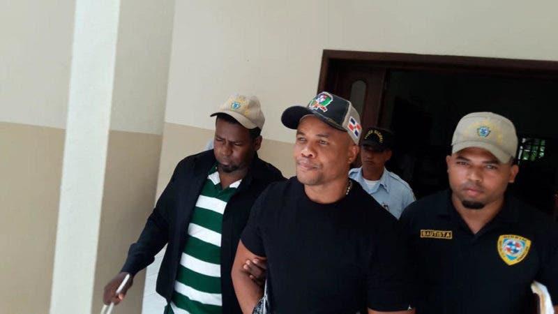 El imputado escoltado  por  otros  agentes policiales  siendo llevado a la carcel preventiva detras del palacio de  justicia