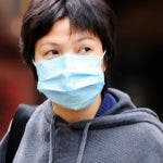 A woman wears a protective mask along a street in Hong Kong on March 13, 2008 amidst flu outbreak in schools in scenes reminiscent of the SARS outbreak in 2003.  Hong Kong education and health officials late on March 12 ordered all primary schools and kindergartens to close for two weeks amid a flu outbreak. Health secretary Chow said the move was a precautionary measure against the spread of influenza in schools.   AFP PHOTO / LAURENT FIEVET