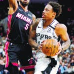 San Antonio Spurs' DeMar DeRozan, right, drives against Miami Heat's Derrick Jones, Jr. during the second half of an NBA basketball game, Sunday, Jan. 19, 2020, in San Antonio. (AP Photo/Darren Abate)