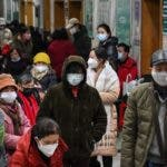 People wearing facemasks to help stop the spread of a deadly virus which began in the city, wait for medical attention at Wuhan Red Cross Hospital in Wuhan on January 25, 2020. - The Chinese army deployed medical specialists on January 25 to the epicentre of a spiralling viral outbreak that has killed 41 people and spread around the world, as millions spent their normally festive Lunar New Year holiday under lockdown. (Photo by Hector RETAMAL / AFP)
