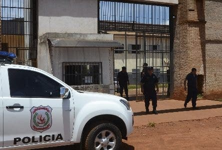 """Police mount guard at Pedro Juan Caballero city jail entrance in Paraguay, Sunday, Jan. 19, 2020. Dozens of inmates escaped from this prison early morning, mostly of Brazil's criminal group PCC, """"Capital First Command"""". (AP Photo/Marciano Candia)"""