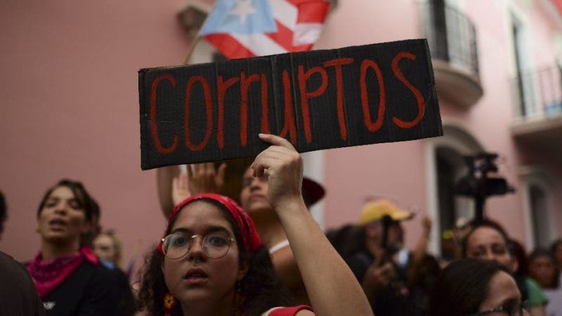"""A young woman holds a sign that reads in Spanish """"Corrupt"""" while protesting outside the executive mansion known as La Fortaleza, in Old San Juan, demanding the resignation of Governor Wanda Vazquez after the discovery of an old warehouse filled with unused emergency supplies in San Juan, Puerto Rico, Monday, Jan. 20, 2020. Anger erupted on Saturday after an online blogger posted a live video of the warehouse in the southern coastal city of Ponce filled with water bottles, cots, baby food and other basic supplies that had apparently been sitting there since Hurricane Maria battered the U.S. territory in September 2017. (AP Photo/Carlos Giusti)"""