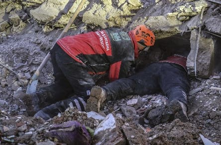 Rescue workers try to save people trapped under debris following a strong earthquake that destroyed several buildings on Friday, in Elazig, eastern Turkey, Sunday, Jan. 26, 2020. Rescue workers were continuing to search for people buried under the rubble of apartment blocks in Elazig and neighboring Malatya. Mosques, schools, sports halls and student dormitories were opened for hundreds who left their homes after the quake. (Ismail Coskun/IHA via AP)