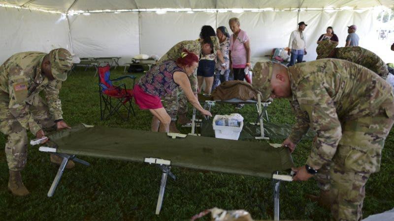 Miembros del ejército de Estados Unidos montan un catre mientras colocan una carpa para albergar a cientos de personas que se quedaron sin un hogar por un sismo, en Guánica, Puerto Rico, el martes 14 de enero de 2020. (AP Foto/Carlos Giusti)