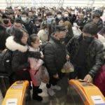 Viajeros equipados con máscaras hacen fila ante los tornos para acceder a una estación de tren en Nantong, en la provincia oriental de Jiangsu, en China, el 22 de enero de 2020. (Chinatopix vía AP)