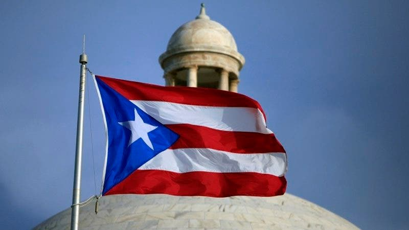 FILE - In this July 29, 2015 file photo, the Puerto Rican flag flies in front of Puerto Rico's Capitol as in San Juan, Puerto Rico. The U.S. territory said Thursday, Nov. 29, 2018, that it has completed its first debt-restructuring deal since the government announced it was bankrupt more than three years ago, giving creditors overall $550 in new bonds for each $1,000 they had held. (AP Photo/Ricardo Arduengo, File)