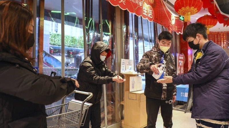 Un empleado distribuye desinfectante a clientes a la entrada de un supermercado en Wuhan, en la provincia de Hubei, en el centro de China, el sábado 25 de enero de 2020, debido a una epidemia de un mortal virus que fecta las vías respiratorias. (Chinatopix vía AP)