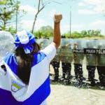 AME6414. MANAGUA (NICARAGUA), 23/02/2020.- Una manifestante grita consignas frente a integrantes de la policía antidisturbios durante una protesta en demanda de justicia este domingo en la catedral de Managua (Nicaragua). EFE/Jorge Torres