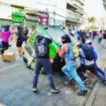 AME7924. VIÑA DEL MAR (CHILE), 25/02/2020.- Manifestantes arrastran un contender de basura durante una jornada de protestas en el marco del Festival Internacional de la Canción este martes, en Viña del Mar (Chile). Cientos de agentes de Carabineros fueron desplegados este martes en la ciudad costera de Viña del Mar para tratar de evitar que volvieran a repetirse los disturbios ocurridos en las jornadas previas aunque no pudieron impedir que centenares de manifestantes incendiaran algunas barricadas y se enfrentaran con varios uniformados. En el marco del festival se están dando movilizaciones, y el domingo, en la jornada inaugural, hubo incidentes que afectaron al Hotel O'Higgins, el más emblemático del festival, que fue evacuado por seguridad y obligó a cambiar la dinámica del certamen musical, como aplazar un día el concurso. EFE/ Alberto Peña
