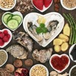 Large aphrodisiac food collection for good sexual health with foods in porcelain bowls and loose on dark oak wood background.