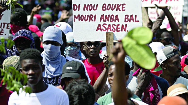 """In this Feb. 12, 2020 photo, a protester holds a sign that reads in Creole """"The people of Martissant are tired of dying from criminals' bullets,"""" referring to one of the capital's most dangerous neighborhoods, during a march against violence in Port-au-Prince, Haiti. Two years after the departure of U.N. peacekeepers, young bandits with automatic weapons randomly halt cars on the main routes in and out of the capital. (AP Photo/Dieu Nalio Chery)"""