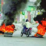 AME7226. PUERTO PRÍNCIPE (HAITÍ), 24/02/2020.- Manifestantes bloquean con barricadas en llamas las calles de la ruta a la casa del presidente de Haití, Jovenel Moise, este lunes, durante una nueva jornada de protestas en Puerto Príncipe (Haití). La capital haitiana vive este lunes una jornada de protestas, barricadas y parálisis en las actividades comerciales, un día después de un cruento tiroteo entre policías y militares registrado en el centro de Puerto Príncipe. La manifestación recorrió avenidas del centro de la capital, congregando a decenas de policías y de civiles, en apoyo a las demandas laborales de los uniformados. EFE/ Jean Marc Hervé Abelard