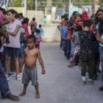 "FILE - In this Aug. 30, 2019 file photo, migrants, many who were returned to Mexico under the Trump administration's ""Remain in Mexico"" program, wait in line to get a meal in an encampment near the Gateway International Bridge in Matamoros, Mexico. A federal appeals court has temporarily halted a major Trump administration policy to make asylum seekers wait in Mexico while their cases wind through U.S. immigration courts. A panel of the 9th U.S. Circuit Court of Appeals in San Francisco ruled Friday, Feb. 28, 2020, in a 2-1 vote to put on hold the policy that furthered President Donald Trump's asylum crackdown. (AP Photo/Veronica G. Cardenas, File)"