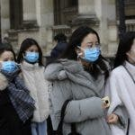 Tourists wearing a mask walks outside the Louvre museum Friday, Feb. 28, 2020 in Paris. . The world is scrambling to get on top of the new coronavirus outbreak that has spread from its epicenter in China to most corners of the planet. Governments and doctors are presenting an array of approaches as the virus disrupts daily routines, business plans and international travel around the world. (AP Photo/Rafael Yaghobzadeh)