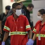 Los empleados del aeropuerto usan máscaras como precaución contra la propagación del nuevo coronavirus COVID-19 mientras trabajan en el Aeropuerto Internacional de Sao Paulo en Brasil, el miércoles 26 de febrero de 2020. (AP Foto / Andre Penner)