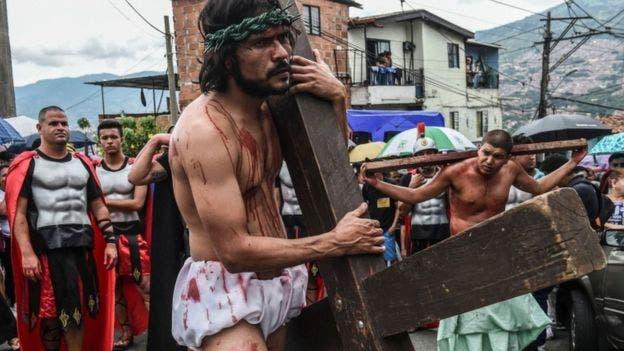 Las representaciones del calvario de Cristo cargando la cruz se repiten en varios puntos del planeta. Esta recreación es del jueves santo en Medellín, Colombia.
