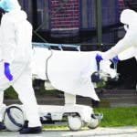 Medical personnel transport a body from a refrigerated container past a carpenter who is building a ramp to the container at Kingsbrook Jewish Medical Center, Wednesday, April 8, 2020, in the Brooklyn borough of New York. The new coronavirus causes mild or moderate symptoms for most people, but for some, especially older adults and people with existing health problems, it can cause more severe illness or death. (AP Photo/Mary Altaffer)