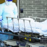 Medical workers wearing personal protective equipment wheel bodies to a refrigerated trailer serving as a makeshift morgue at Wyckoff Heights Medical Center, Monday, April 6, 2020, in New York. The new coronavirus causes mild or moderate symptoms for most people, but for some, especially older adults and people with existing health problems, it can cause more severe illness or death. (AP Photo/John Minchillo)