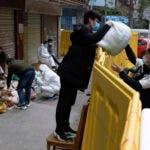 Un vendedor entrega una bolsa de alimentos a un cliente. Foto AP.